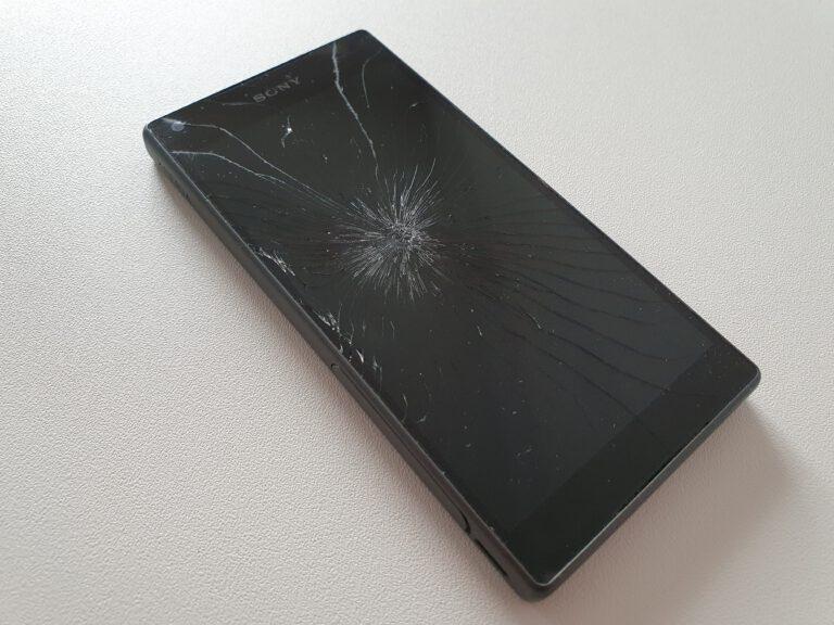 Ein schwarzes Handy, dessen Display in der Mitte gesprungen ist.