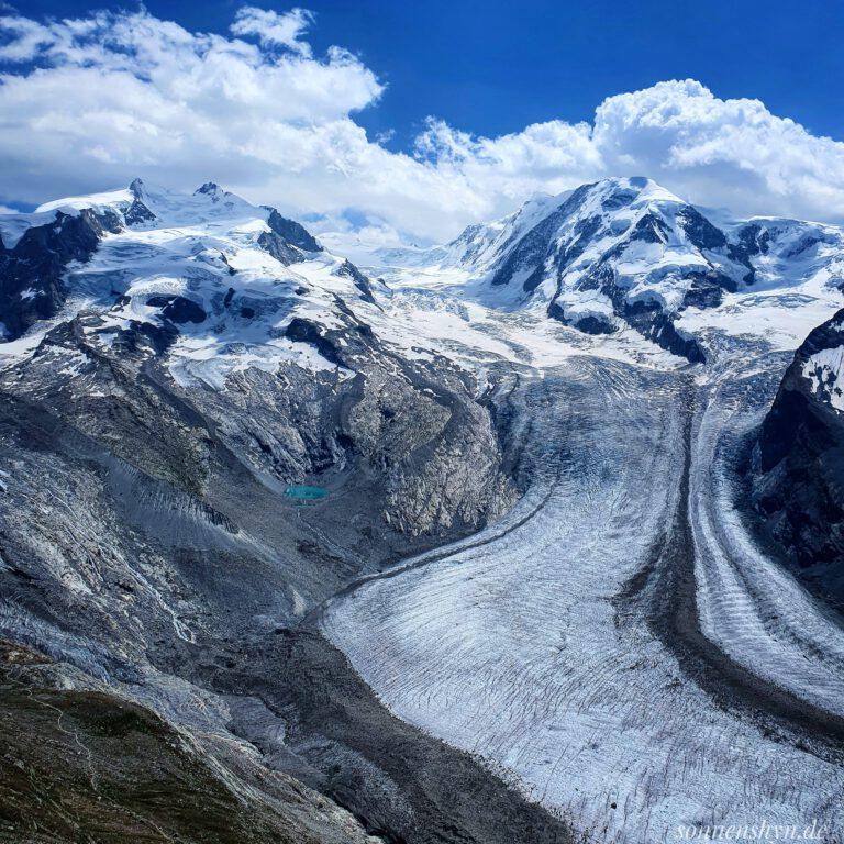 Der Gornergletscher in Zermatt/Schweiz - Weiße, leicht schneebedeckte Berge. Weiße Wolken und ein blauer Himmel.