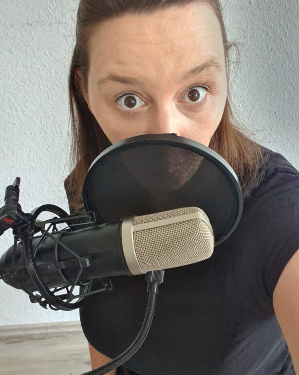 Ich, die ihr Gesicht hinter einem großen schwarz grauen Mikrofon fast komplett versteckt hat. Ich mache große gespielt erschrockene Augen. Meine braunen Haare sind zum Zopf gebunden.