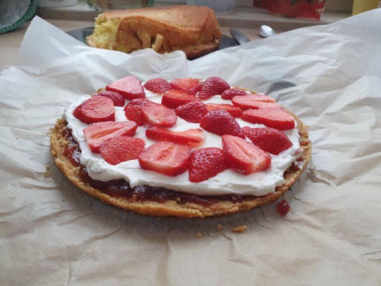 Ein Kuchen belegt mit weißer Creme und Erdbeeren.