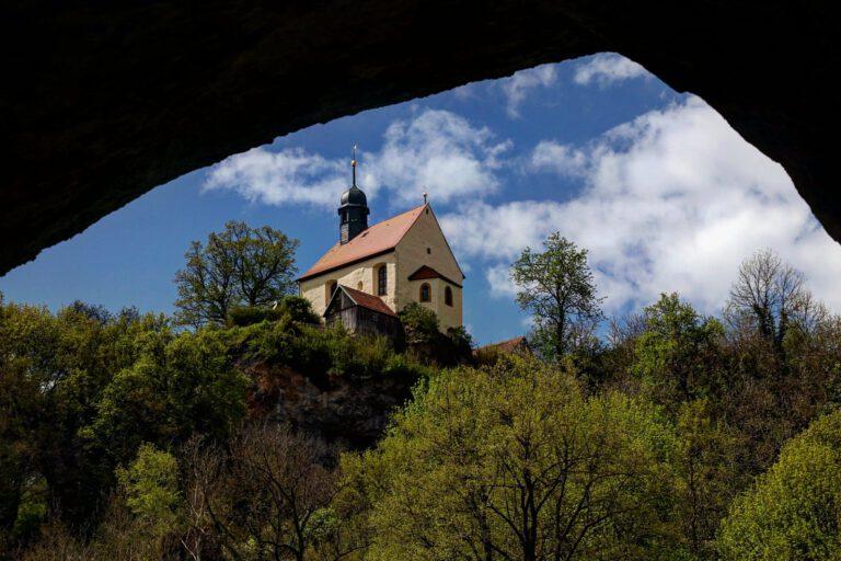 Eine Kapelle auf einem Berg von unten aus einer Höhle heraus fotografiert.