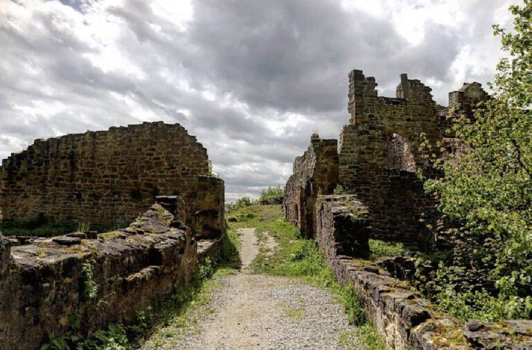 Die Mauern einer Burgruine zu der eine kaputte Steibrücke führt.