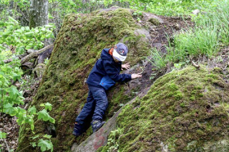 Ein Kind klettert zwischen Felsen.