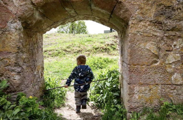 Ein kleines Kind, das durch ein gemauertes Tor läuft.