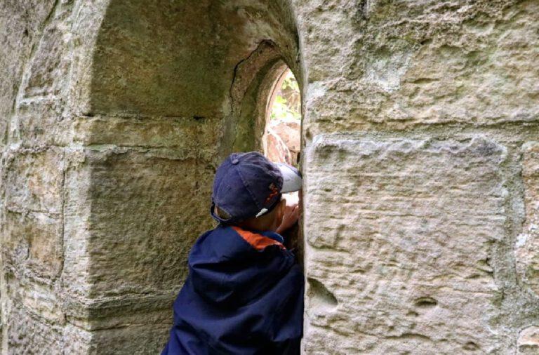 Ein Kind, dass durch einen Spalt einer Burgmauer schaut.