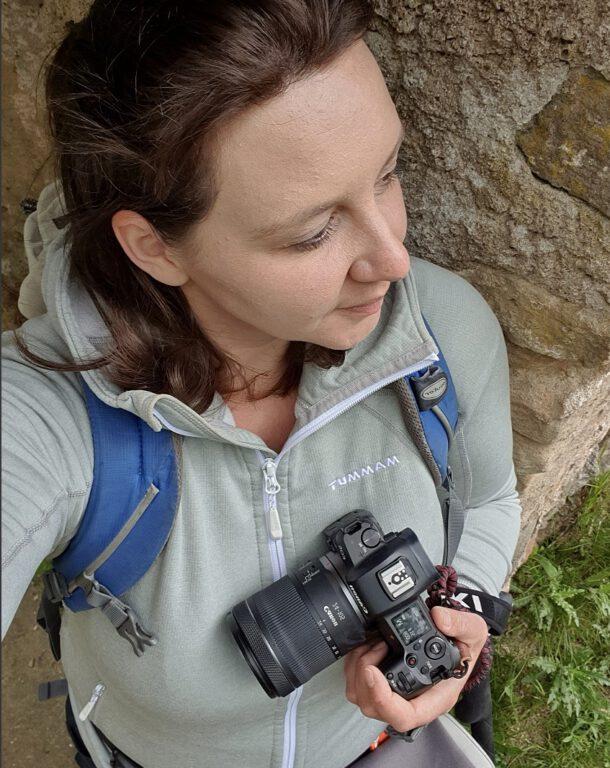 Ich in einer grauen Wanderjacke wie ich mit meiner schwarzen Kamera in der Hand in die Ferne schaue.