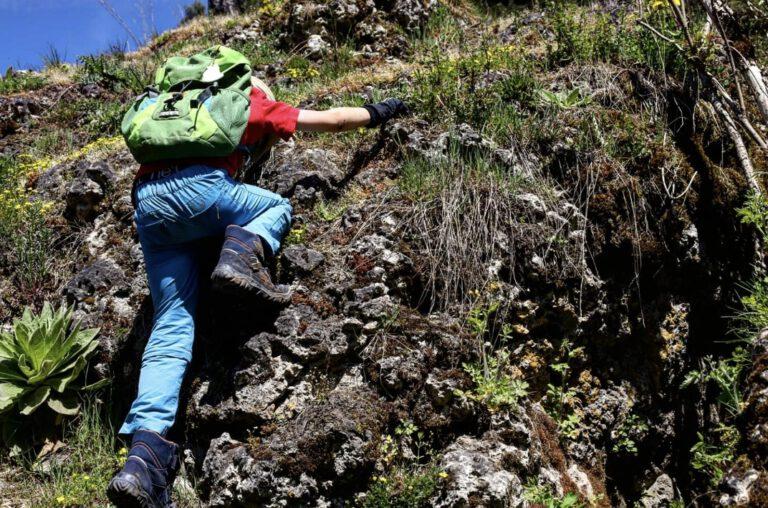 Ein Kind klettert einen Felsen hoch.