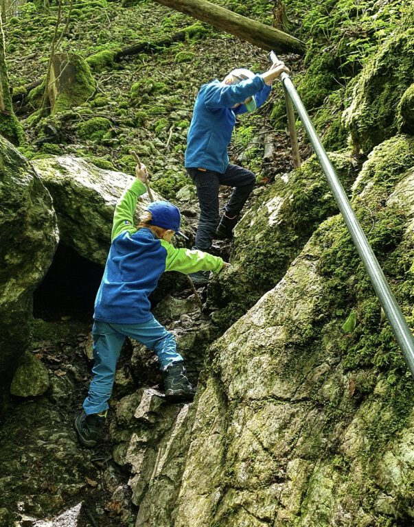 2 Kinder klettern zwischen Felsen.