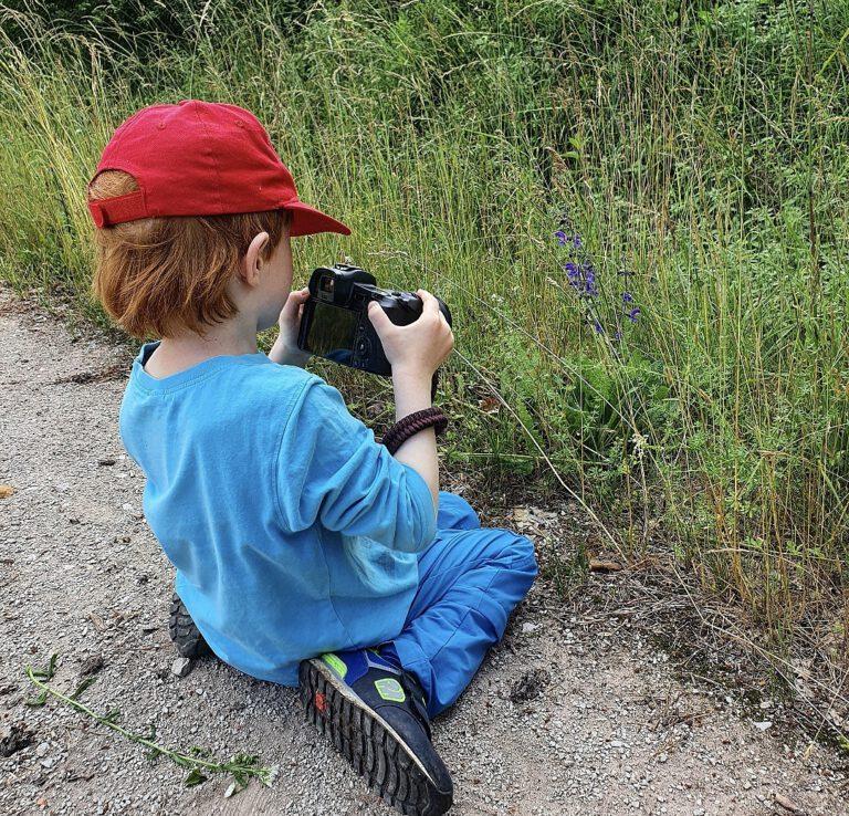 Mein Mittlerer auf dem Boden sitzend. Er hat meine Kamera in der Hand und fotografiert eine lila Blume.