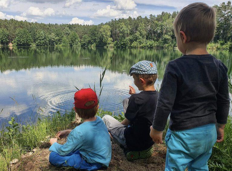 Meine drei Kinder die an einem See sitzen bzw stehen. Der See ist von hohen Bäumen umgeben.