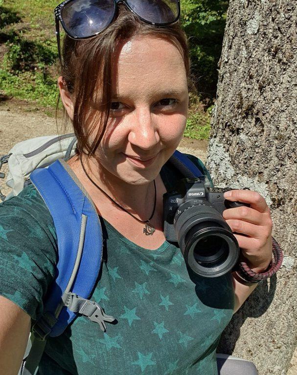 Ich trage ein grünes Shirt mit Sternen drauf, habe meine Canon in der Hand und mache ein Selfie von mir.