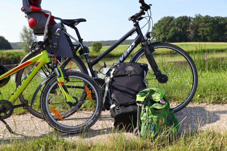 Ein großes und ein kleines Fahrrad an denen 2 Rucksäcke lehnen.