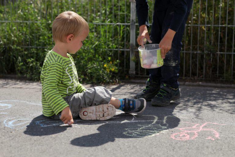 2 Kinder malen mit Kreide.