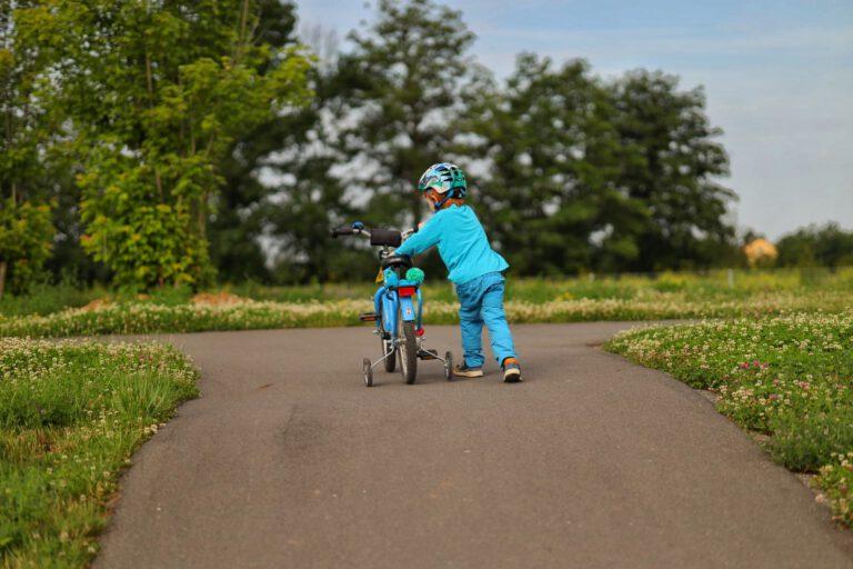Ein Kind schiebt ein Fahrrad den Berg hinauf.