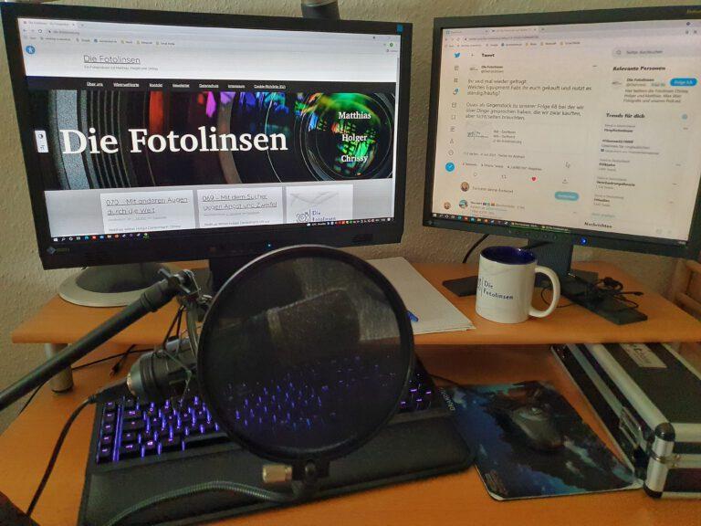 Ein Schreibtisch mit 2 Monitoren, einer Tastatur und Mikrofon.