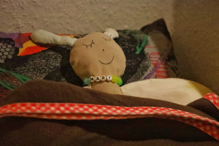 Ein Schmetterlingstofftier, welches eingekuschelt im Bett liegt