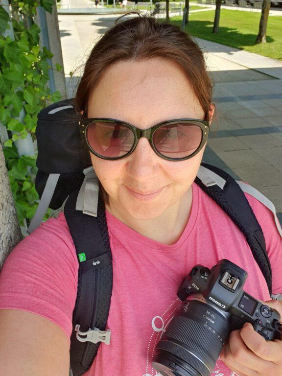 Ich mit rosa Shirt, Haare zusammengebunden, schaue ich die Handykamera und halte meine Canon in der Hand