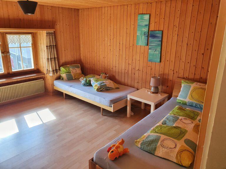 Ein Zimmer mit zwei Betten und bunter Bettwäsche.