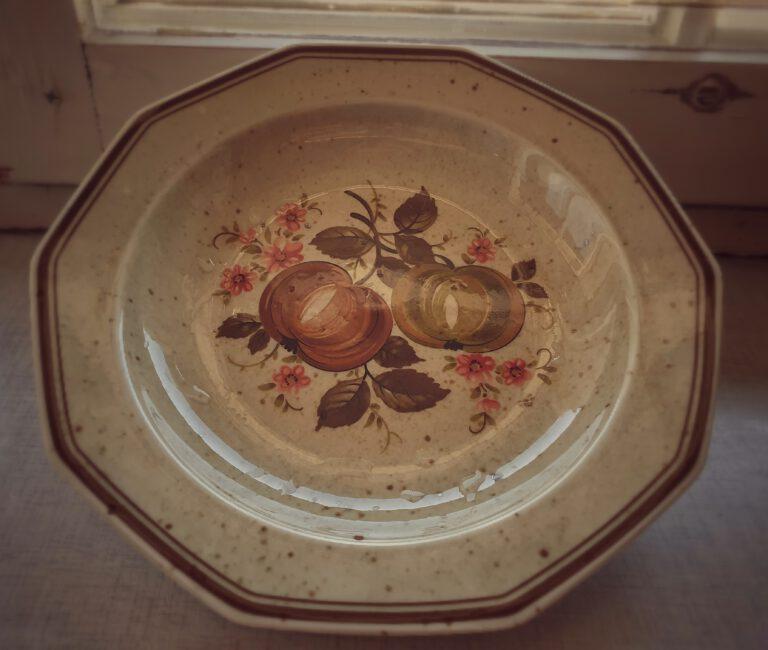 Ein alter Teller mit Gemüse als Muster