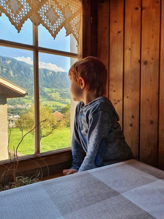 Ein Kind schaut aus dem Fenster in die Berge.