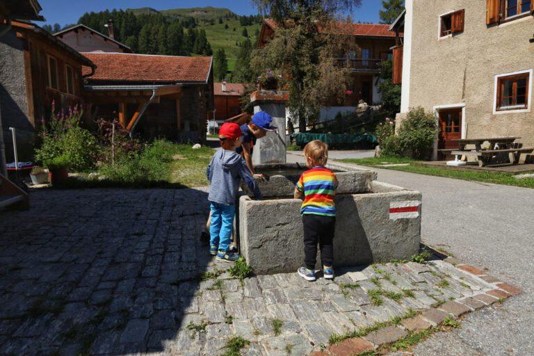 3 Kinder an einem Brunnen