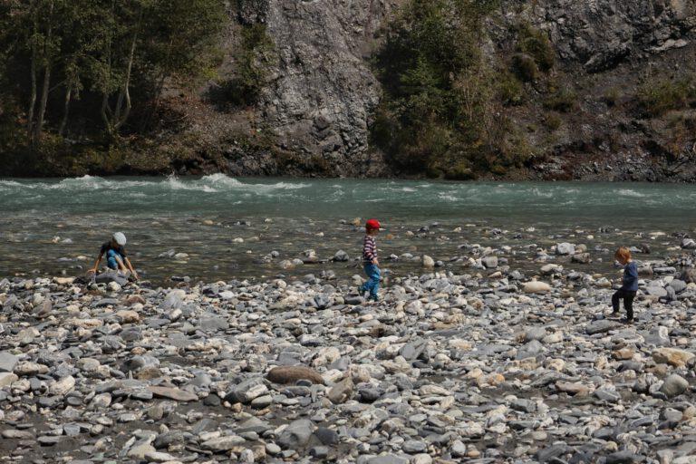 3 Kinder spielen am Ufer des Rheins mit Steinen