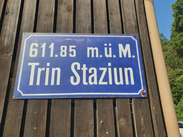 """Ein blaues Schild mit weißer Schrift """"611.85 m.ü.M. Trin Stazium"""""""