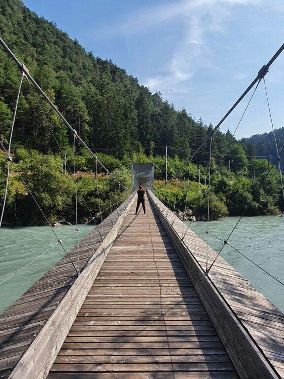 Ich stehe in der Mitte einer Holzhängebrücke. Rechts und links sieht man den blau grünen Rhein.