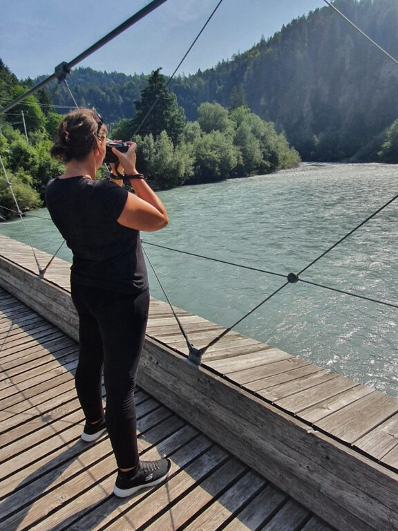 Ich in schwarz gekleidet seitlich von hinten fotografiert, wie ich auf einer Holzhängebrücke stehe und den blau grünen Rhein fotografiere.