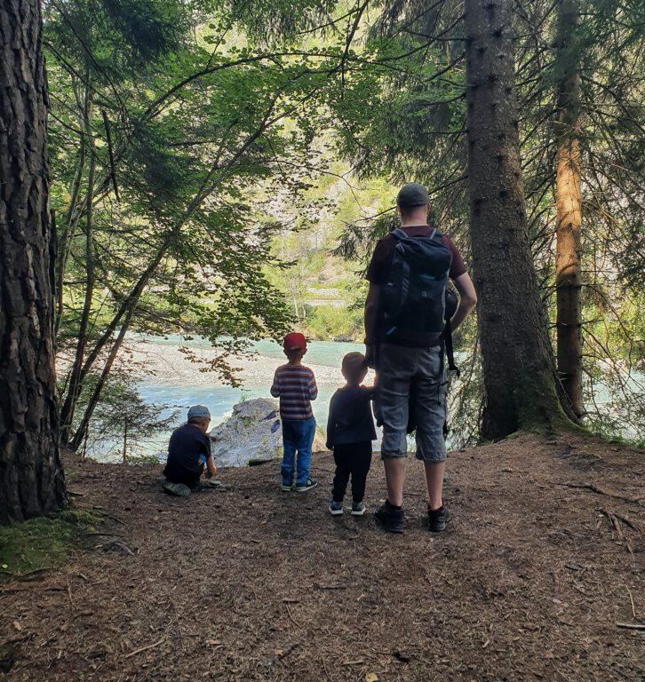 3 Kinder und ein Mann im Wald schauen auf den Rhein
