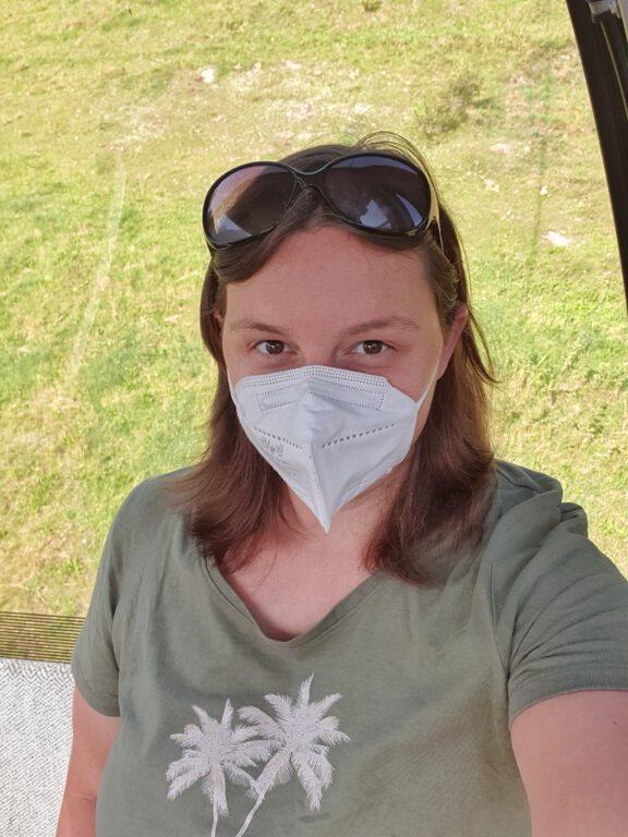 Ein Selfie von mir in einer Gondel. Ich trage eine weiße Maske und ein grünes Shirt.