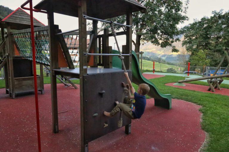 Ein Kind klettert auf einem Spielplatz eine Kletterwand hoch