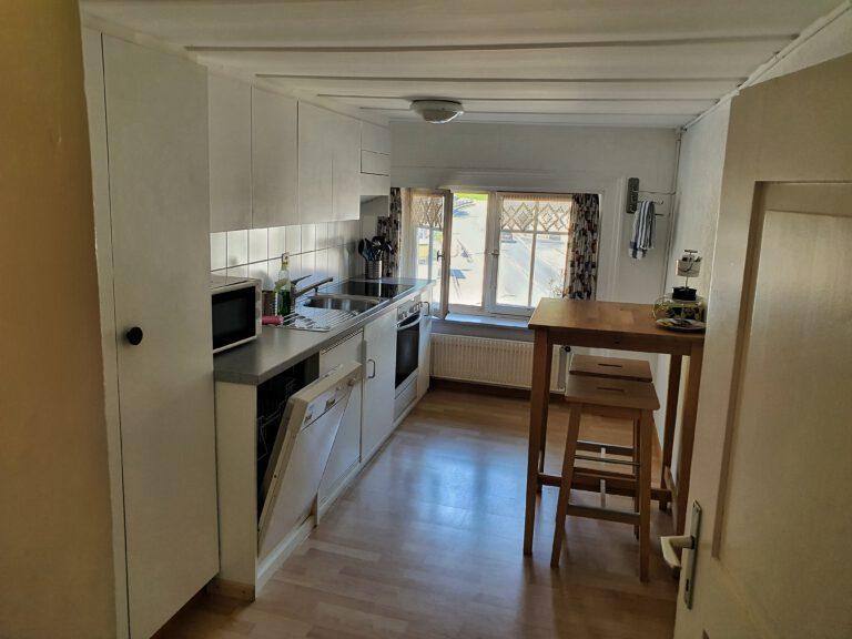 Eine Küchenzeile und ein hoher Esstisch.