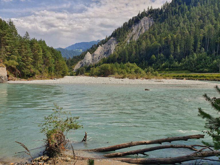 Blau grünes Gewässer umgeben von Bergen und Nadelbäumen. Etwa in der Mitte ist ein Steinstrand.