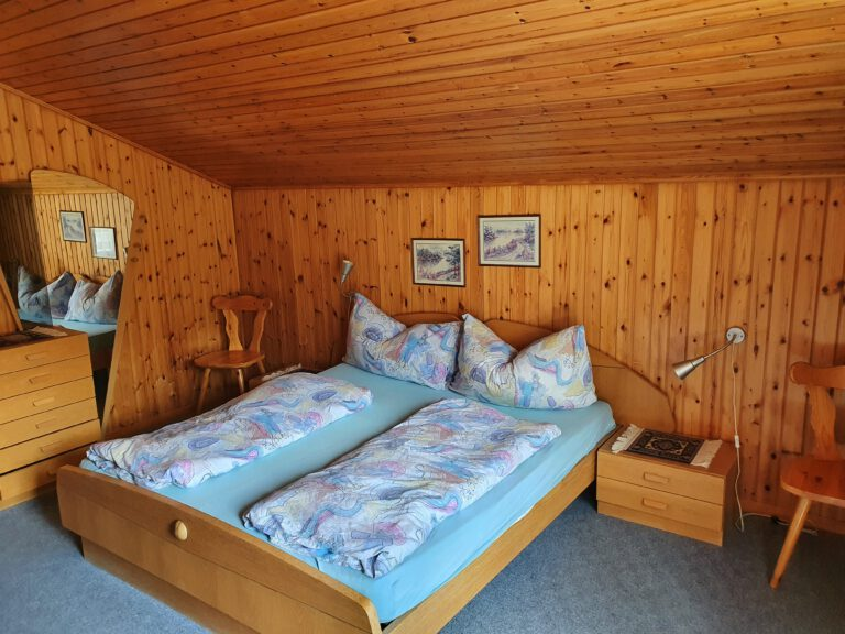 Ein Doppelbett in einem Zimmer mit Holzwänden und Decken