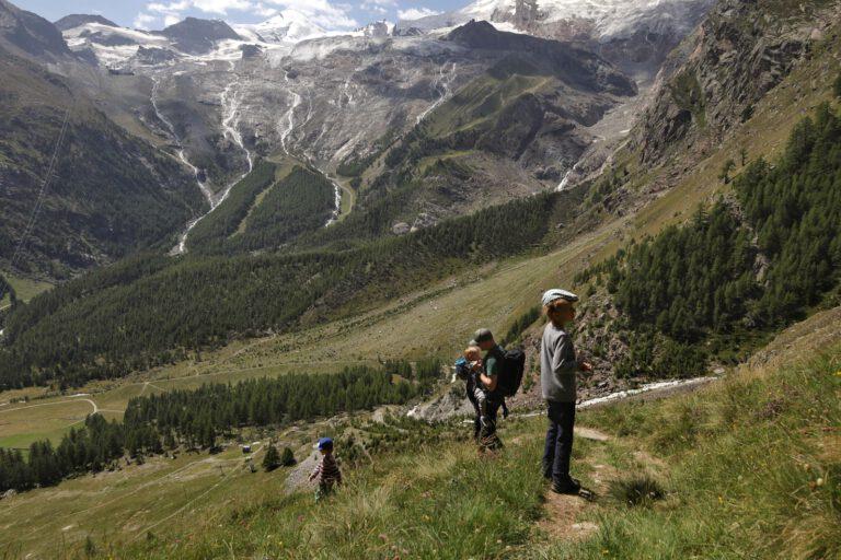 3 Personen stehen auf einen Berg und schauen sich andere Berge an