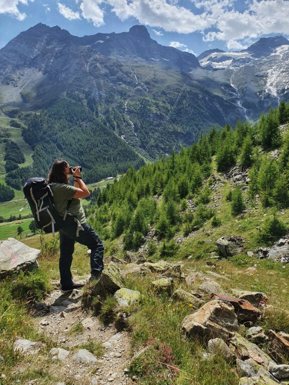 Ich stehe auf einer grünen Wiese und fotografiere die Berge