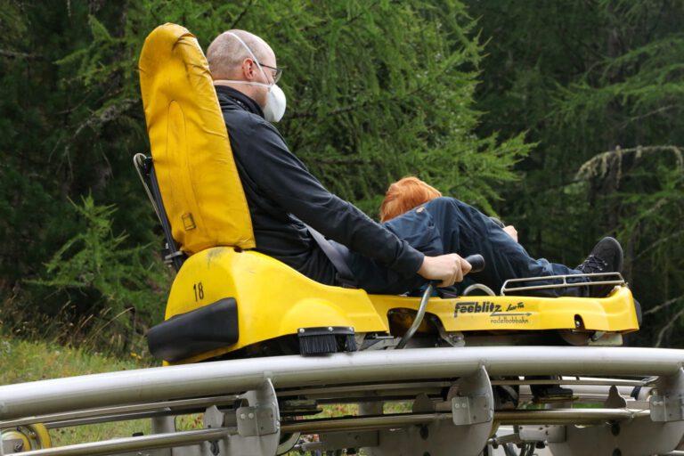 Ein Mann und ein Kind in einer gelben Sommerrodelbahn