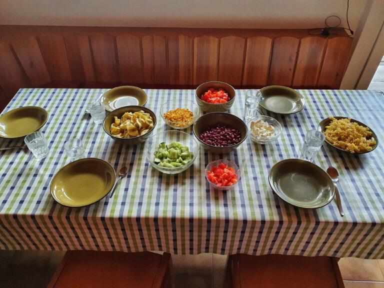 Ein Tisch mit vielen Schüssel. Tortellini, Gurken, Tomaten, Kidneybohnen, Paprika, Mais, Schafskäse und Nudeln
