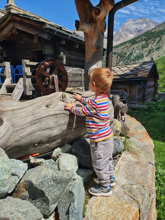 Ein Kind an einem Brunnen mit Wasserrad