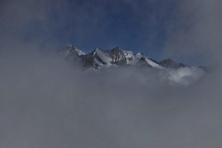 Dichte Wolken die ein kleines Fenster um schneebedeckte Gipfel liefern