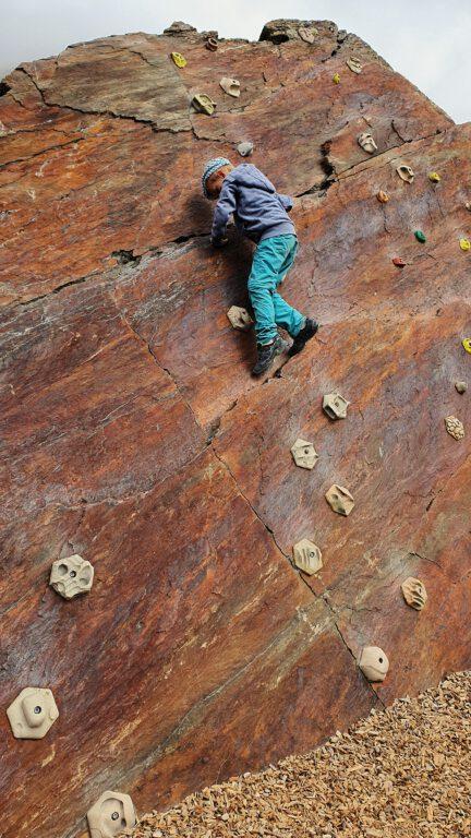 Eine Kletterwand mit einem Kind das nach oben klettert