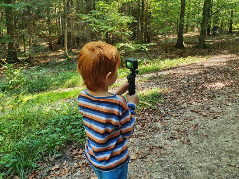 Ein Kind trägt eine GoPro im Wald und filmt.