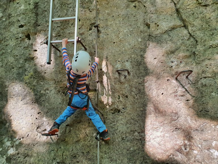 Ein kleines Kind hängt am Felsen und versucht eine Leiter hochzuklettern.