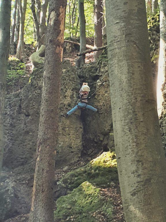 Ein Kind hängt mit Kletterausrüstung am Felsen.