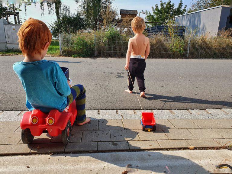 Zwei Kinder spielen auf der Straße mit Autos.