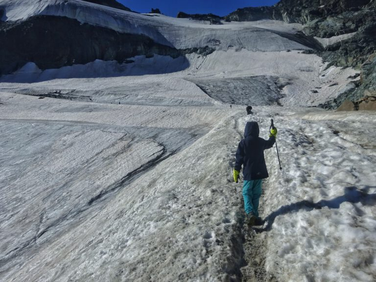 Ein Kind mit Wanderstock auf einem Berg im Schnee