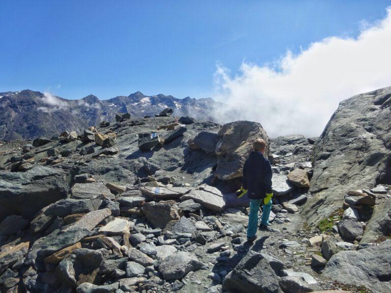 Ein Kind im Geröll eines Berges, das auf eine Wolke zuläuft