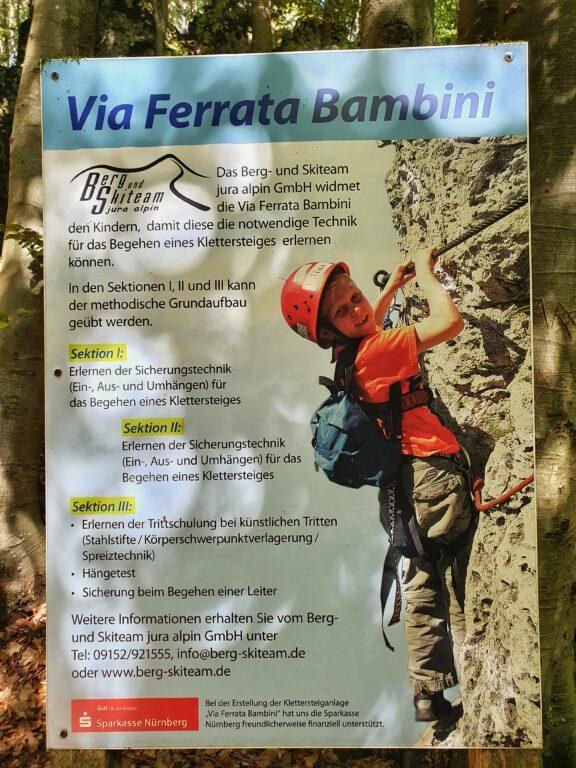 """Ein Schild mit der Aufschrift """"Via Ferrata Bambini"""" - Man sieht ein Kind in Kletterausrüstung an einem Felsen."""