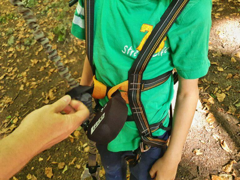 Ein Kinderklettergeschirr, welches auf Sicherheit geprüft wird.